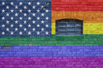 A mural of the Rainbow PRIDE Flag overlays the USA flag
