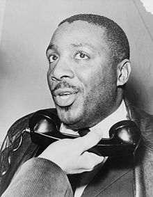 A photo of Civil Rights activist Dick Gregory talking on the phone circa 1968